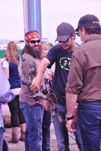 Luke Bryan prepping his bow while Jep Robertson looks on.